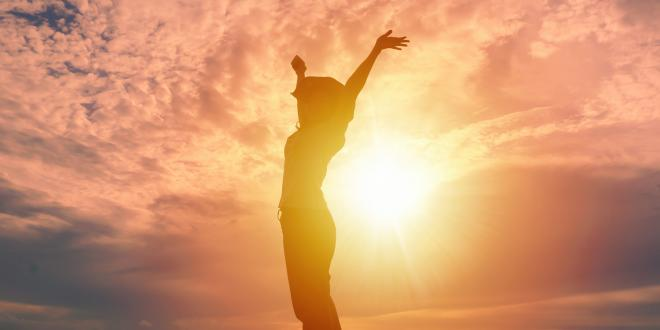 Happy woman raising hands up and beautiful sunrise in background.