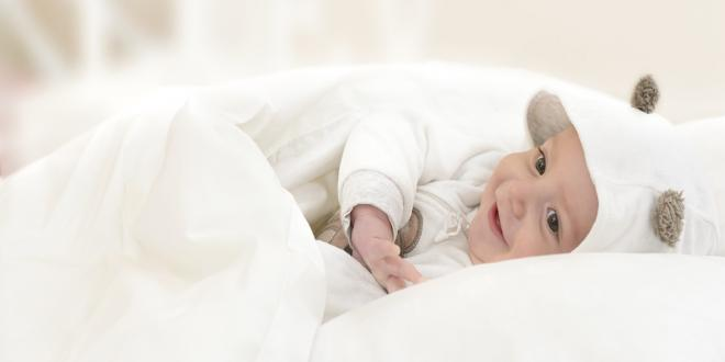 A happy baby smiling snuggled in a white blanket
